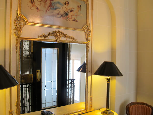The vintage art deco lift is reflected in a hallway mirror at the Millennium Hotel Paris Opera
