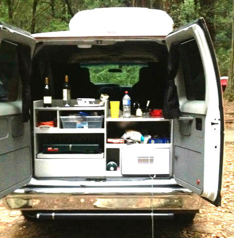 The back of the van doubles as a kitchen, with mini fridge, sink, gas stovetop, and cooking supplies.