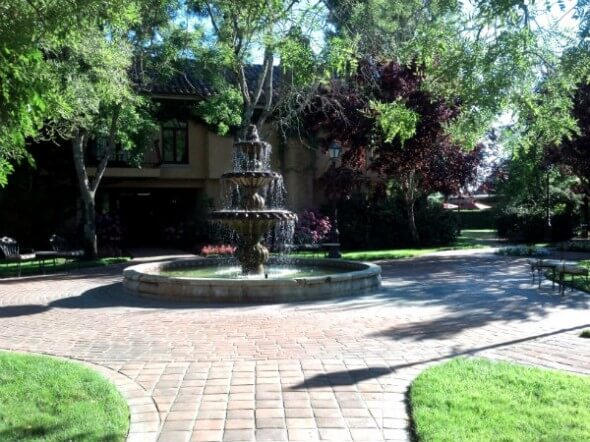 The grounds are beautifully landscaped with fountains and manicured lawns.