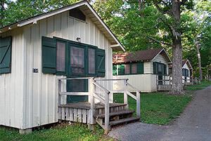 Cottages set back in stands of hardwood trees.