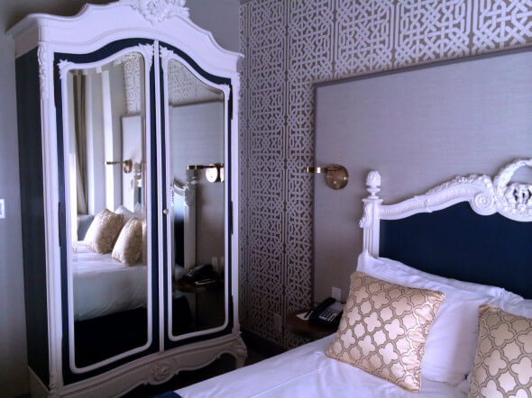 A deluxe room with the original 1913 armiore and headboard