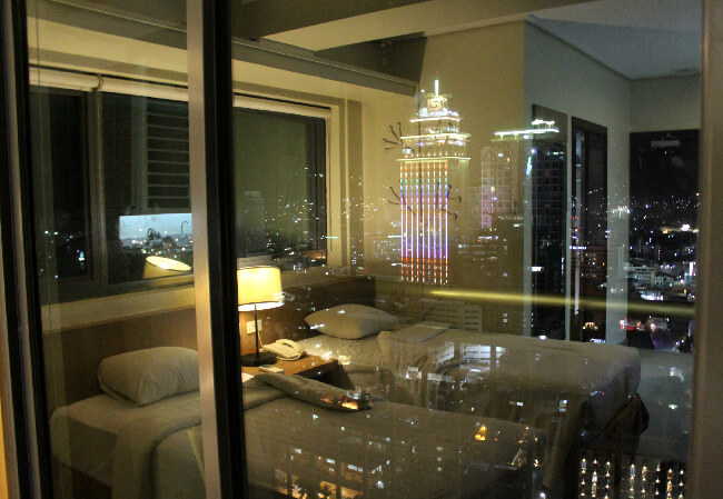 Our room on 33rd floor at night. The neon lights are on the outside of the Crowne Regency Hotel.