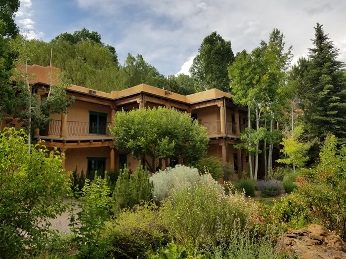 El Monte Sagrado Resort in Taos is set amidst lush greenery and a mountain backdrop.