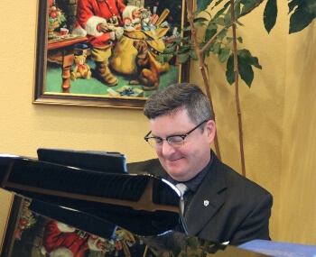 Dr. Eric J. Littleton plays carols on the Grand piano in Pigeon Forge