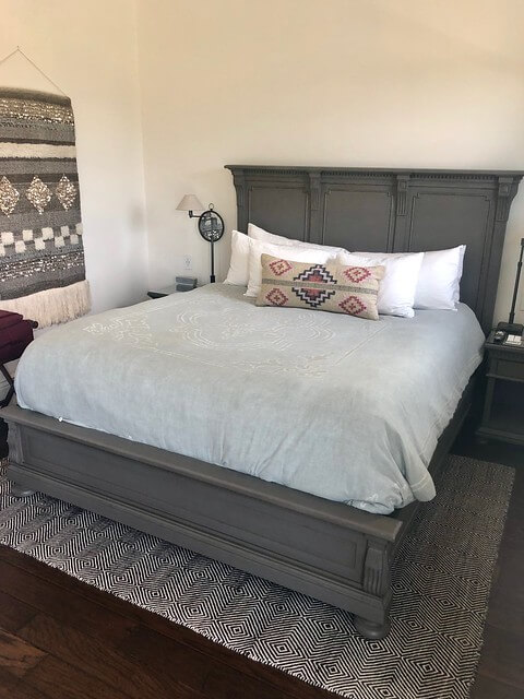 Antiqued grey oak bed frame on king bed, decorative tapestry on wall.