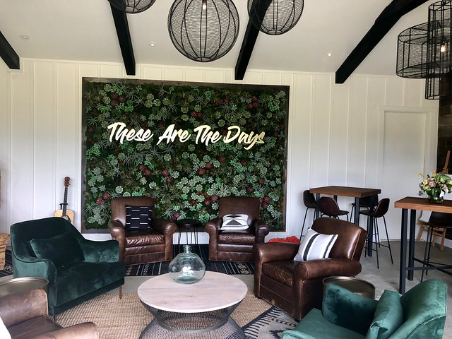 Leather chairs, living plant wall and table complete the indoor/outdoor living room in the backyard barn.