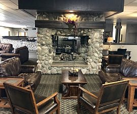 Brown leather chairs in front of river rock stone fireplace at Billings Hotel in Montana.