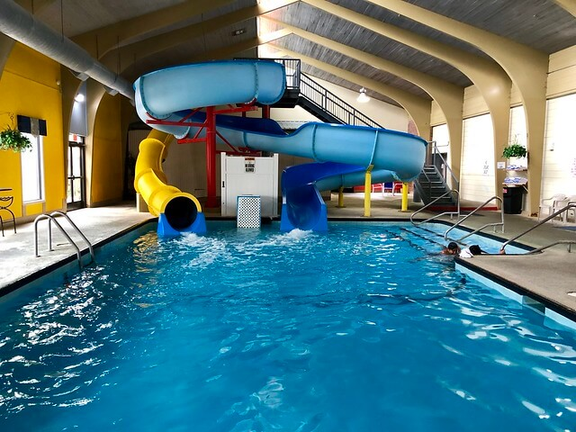 Two waterslides, one enclosed and one open, feed into the indoor swimming pool at the hotel.
