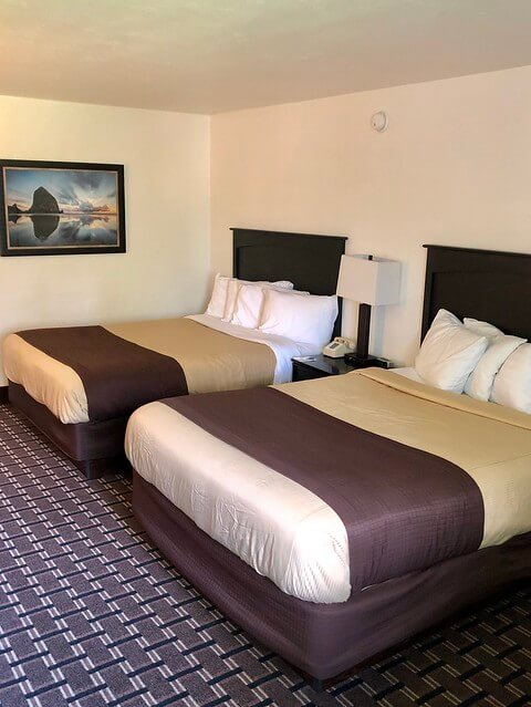 Two queen beds and a small table with desk lamp at Billings Hotel