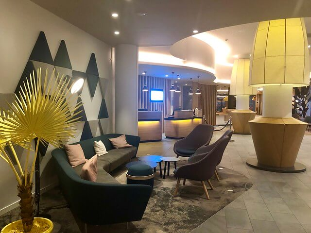 Holiday Inn Express Paris hotel lobby with giant, over-sized lamps and black large sofa.