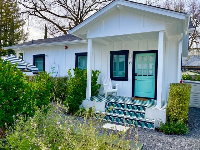 The back entrance to Bungalow B offers privacy, a white Adirondack chair and brightly colored porch.