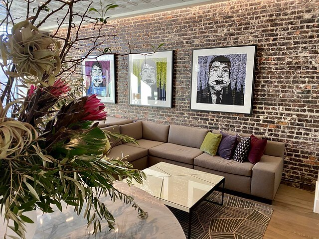 Hotel Cerro lobby with exposed red brick, modern artwork and fresh flowers.