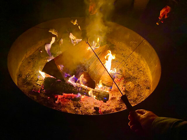 Hotel guests roast marshmallows over blazing logs above a fire pit at Rush Creek Lodge Yosemite in California.