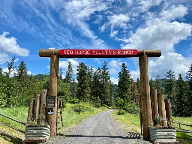 Heavy wood beam with Red Horse Mountain Ranch spelled-out welcomes guests to the all-inclusive guest ranch in north Idaho.
