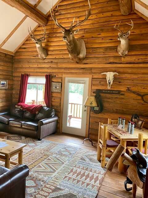 Eagle's Nest log cabin includes mounted deer and elk heads, leather furniture and Western style rugs.