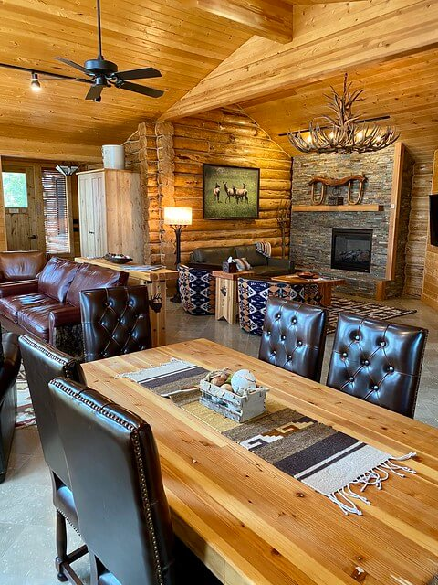 Rustic luxury at Elk Lakeside Cabin with dark leather chairs, wood dining table, rock fireplace in living room with elk shed chandelier.