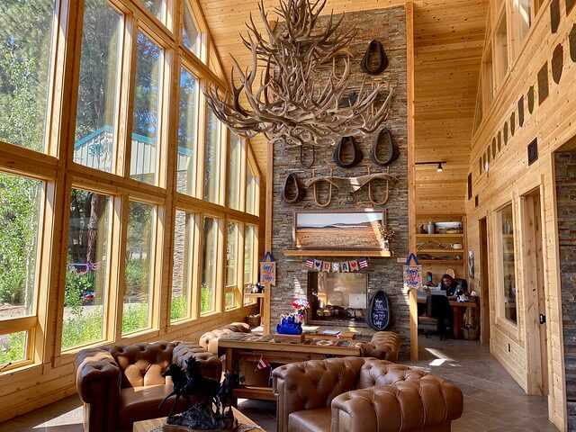 Wall of glass window panes, floor to ceiling stone fireplace and antler chandelier hang at Silvies Valley Ranch gate house.